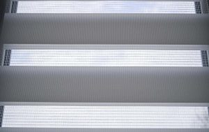 stock photo white roller blinds with stripes and mesh on a plastic window in the room day and night system it