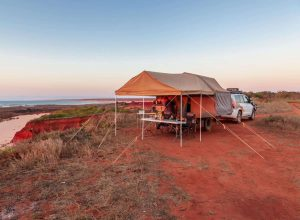 stock photo man preparing a meal in offroad camper trailer while camping on top of the red cliffs at james